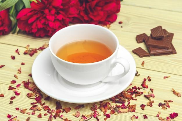 Kopje groene thee op tafel met verse pioen bloemen