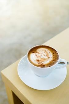 Kopje hete latte koffie met mooie melkschuim latte art textuur op houten tafel.