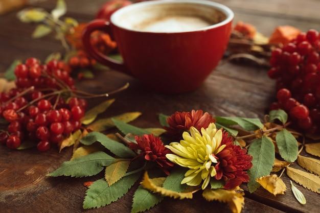 Kopje hete latte op de herfstmuur. herfstboeket op het houten ruwe oppervlak.