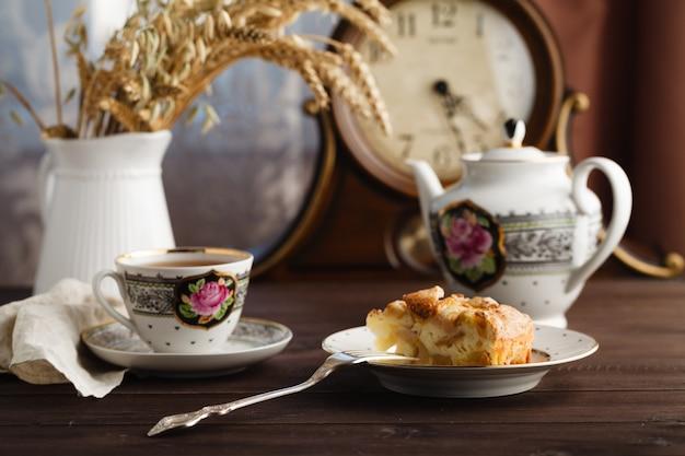 Kopje hete thee, een theepot en een deel van een appeltaart op een tafel