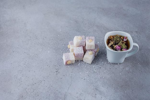 Kopje hete thee en zoete lekkernijen met noten op stenen achtergrond.