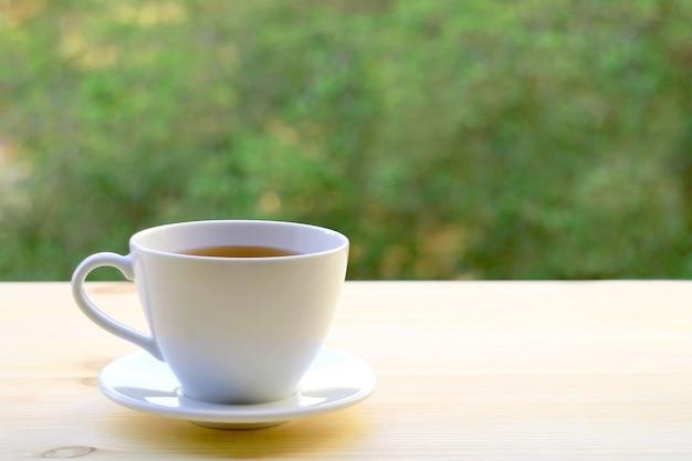 Kopje hete thee geïsoleerd op buitentafel met wazig gebladerte op de achtergrond