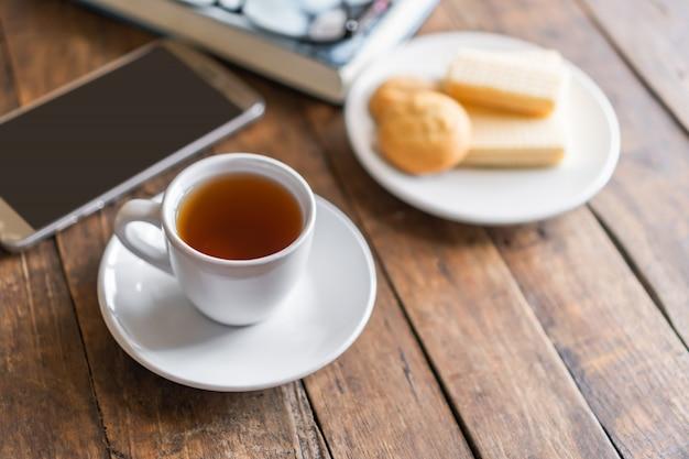 Kopje hete thee met stoom en wafels snack, oude dikke boek met bril op oude tafel vloer en vervagen raam licht in de woonkamer