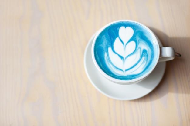 Kopje hete vlinder erwt latte of blauwe spirulina latte op houten tafel
