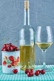 Kopje kersen, fles witte wijn en glas op blauwe ondergrond