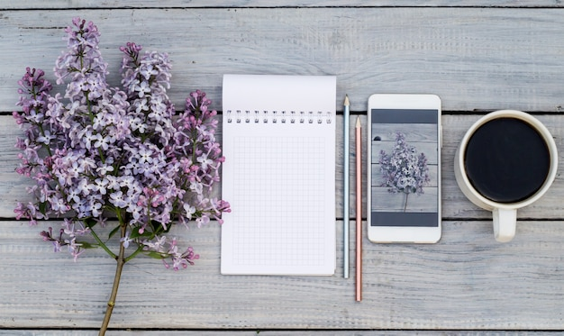 Kopje koffie, blocnote, een lila tak en telefoon met dezelfde sering op witte houten tafel