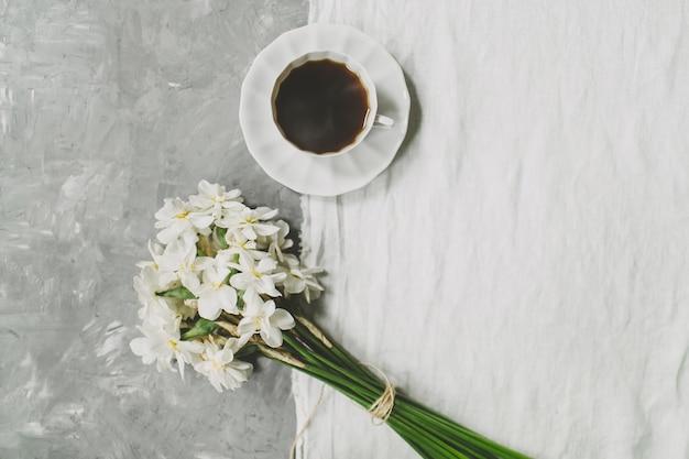 Kopje koffie, boeket van narcis bloemen op gestructureerde grijze en witte linnen achtergrond.