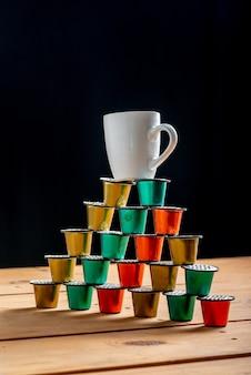 Kopje koffie bovenop een toren gemaakt met gekleurde koffiepads en gebruikt op houten tafel on