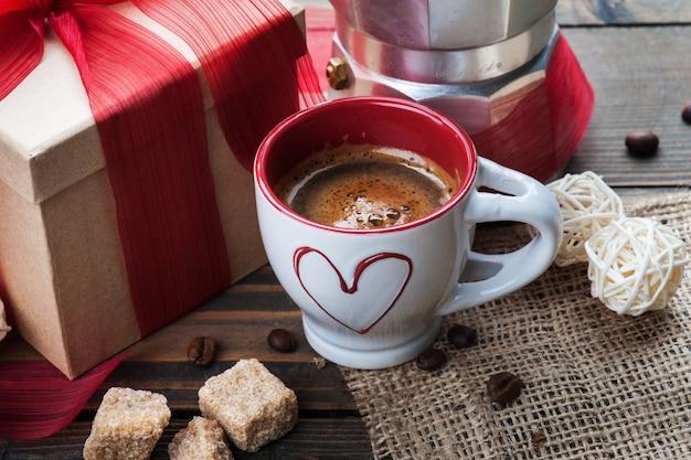 Kopje koffie, cadeau met rood lint, bruine suiker