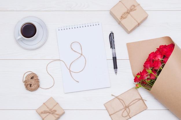 Kopje koffie, cadeau of cadeautjes dozen, rozen, notitieboekje met pen op witte houten tafel. plat leggen, vrouw dag concept,