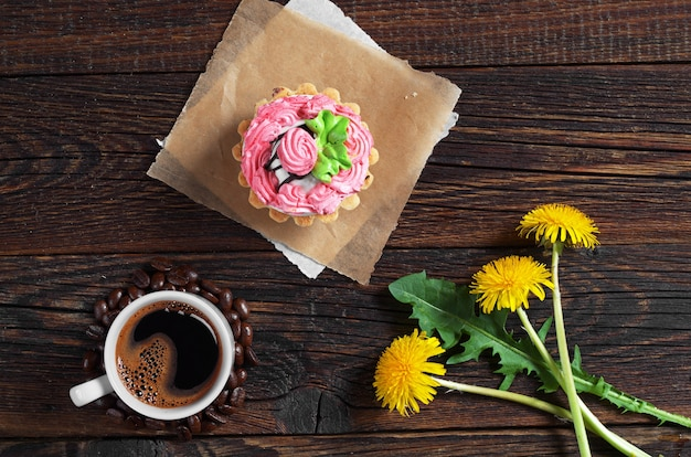 Kopje koffie, cake en bloemen op donkere houten tafel, bovenaanzicht