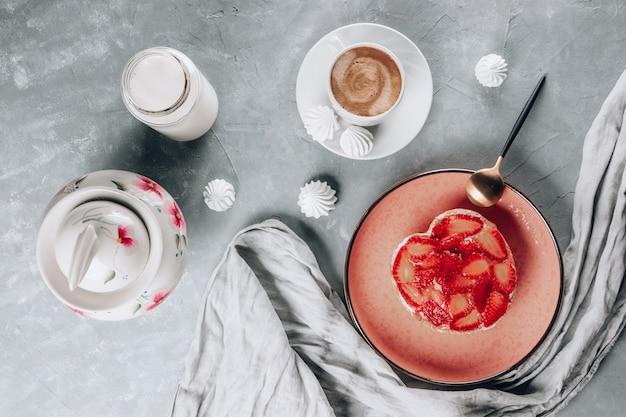 Kopje koffie, cake met aardbeien, melk en schuimgebak op een grijze tafel
