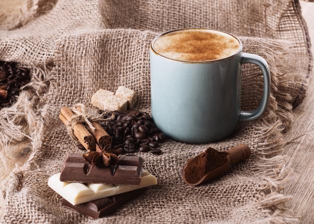 Kopje koffie, chocolade, bonen, anijs en kaneel op houten achtergrond
