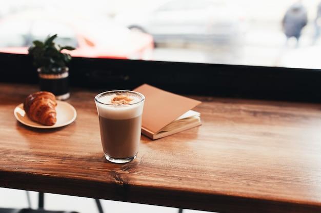 Kopje koffie, croissant aan tafel bij het raam in café. onscherpe achtergrond.