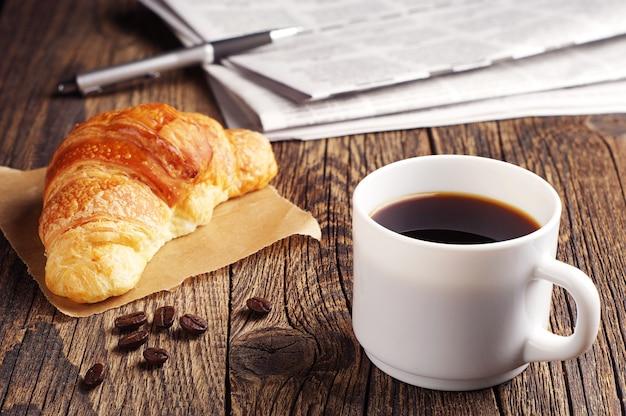Kopje koffie, croissants en krant op houten tafel
