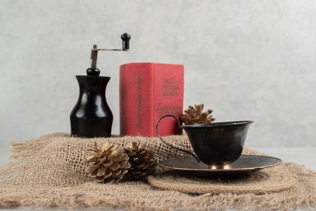Kopje koffie, dennenappels en boek over jute