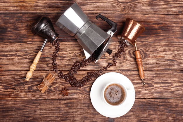 Kopje koffie, drie koffiepotten, kaneel, anijs, koffiebonen op een houten dienblad