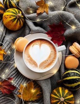 Kopje koffie, droge bladeren en sjaal op een tafel. plat leggen, bovenaanzicht, kopie ruimte