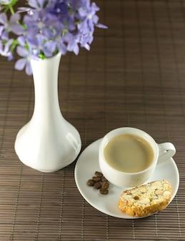 Kopje koffie en biscotti naast bloemenvaas