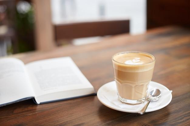 Kopje koffie en boek op tafel in straatcafé