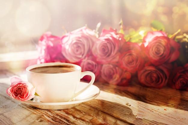 Kopje koffie en boeket roze rozen op tafel
