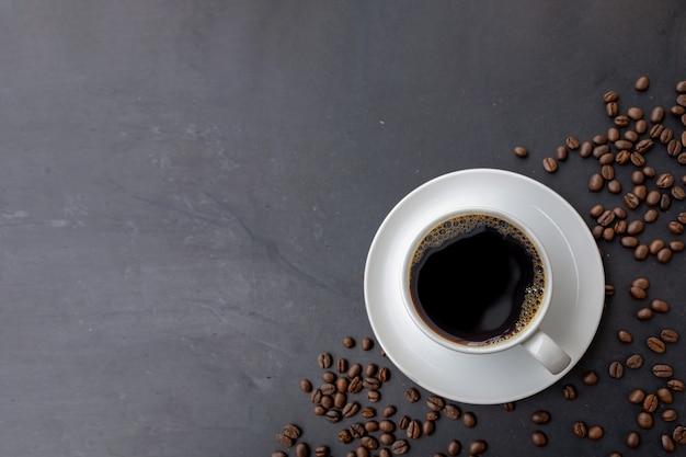 Kopje koffie en bonen op zwarte houten tafel muur. bovenaanzicht