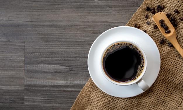 Kopje koffie en bonen op zwarte houten vloer muur. bovenaanzicht