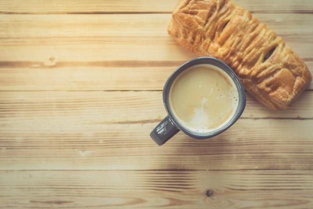 Kopje koffie en broodje op houten tafel, bovenaanzicht, pagina met kopie ruimte. voeding, calorieën, dessert thema