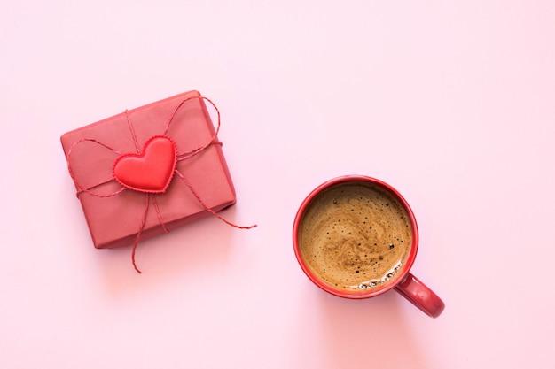 Kopje koffie en cadeau met liefde op pastelroze. bovenaanzicht valentijnsdag kaart.