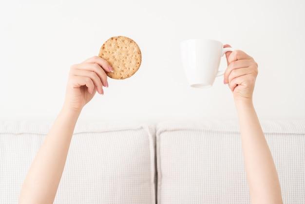 Kopje koffie en cake in handen boven een deken in bed. vrouw wakker in de ochtend
