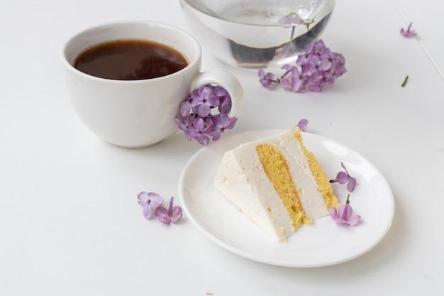 Kopje koffie en cakehoorns van stilleven met een boeket seringen op een witte tafel een kopje koffie een bord met een fluitje van een cent internationale vrouwendag 8 maart