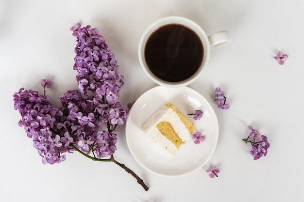 Kopje koffie en cakehoorns van stilleven met een boeket seringen op een witte tafel, een kopje koffie, een bord met een fluitje van een cent. internationale vrouwendag, 8 maart