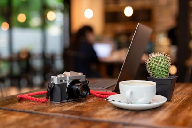 Kopje koffie en camera met laptop op houten tafel.