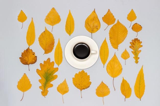 Kopje koffie en collectie, set herfst gele bladeren op grijs, herfst behang