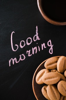 Kopje koffie en cookie op een donkere achtergrond. inscriptie goede morgen.