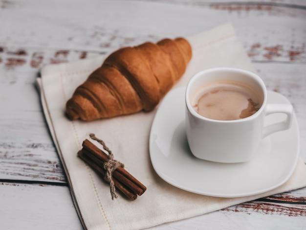 Kopje koffie en croissant met kaneelstokjes op servet op een houten tafel