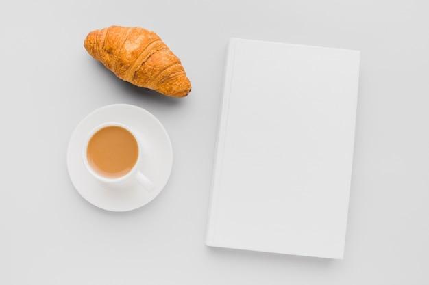Kopje koffie en croissant naast boek