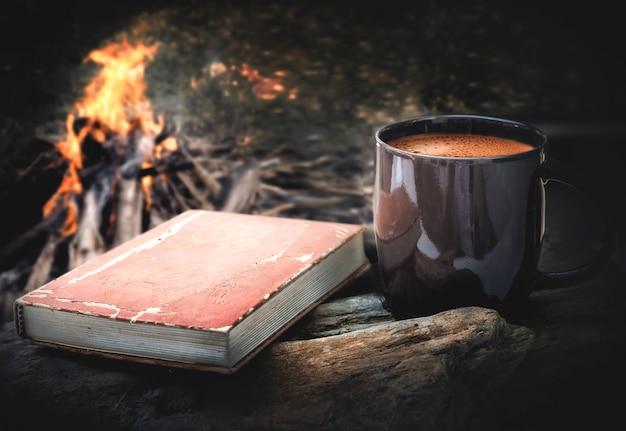 Kopje koffie en een boek met kampvuur nacht achtergrond.