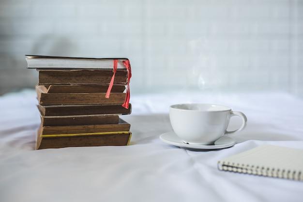 Kopje koffie en een boek op een bed. witte kop met koffie op een boek. detailopname