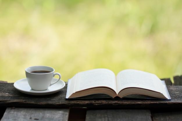 Kopje koffie en een boek op een houten tafel.