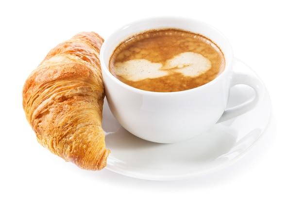 Kopje koffie en een croissant op een witte achtergrond