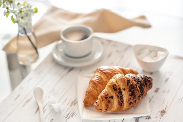 Kopje koffie en een croissant op een witte tafel