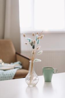 Kopje koffie en een transparante vaas met gedroogde bloemen op witte achtergrond