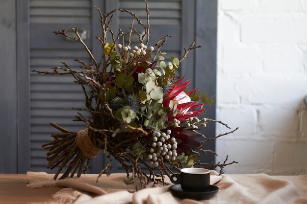 Kopje koffie en exotische boeket zonder verpakking staat op tafel met beige linnen tafellaken, vakantie ochtend concept
