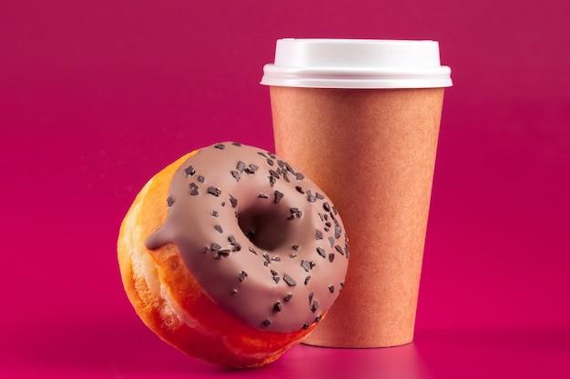 Kopje koffie en geglazuurde ronde donut op een roze achtergrond