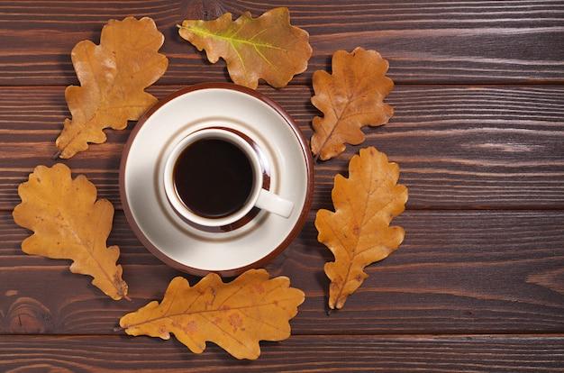 Kopje koffie en gele herfstbladeren