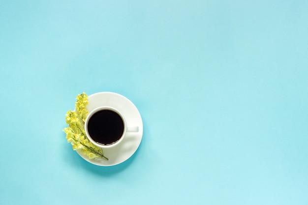 Kopje koffie en gele wilde bloemen, blauw papier achtergrond concept goedemorgen of hallo lente
