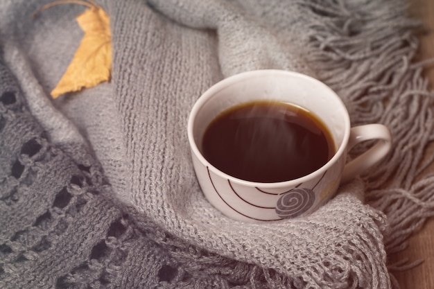 Kopje koffie en grijs gebreid. herfst concept.