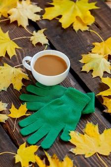 Kopje koffie en groene handschoenen naast esdoornbladeren op houten tafel.