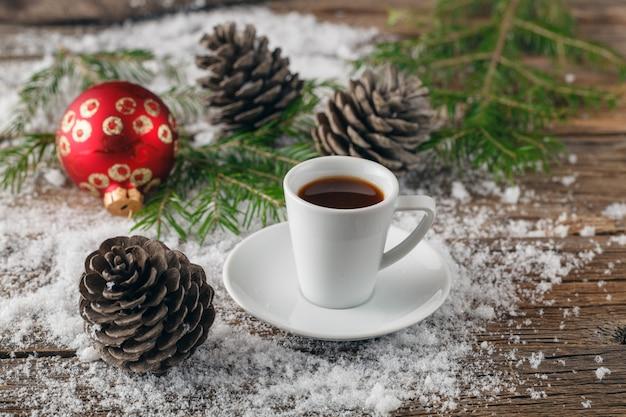 Kopje koffie en kerst speelgoed op houten tafel.
